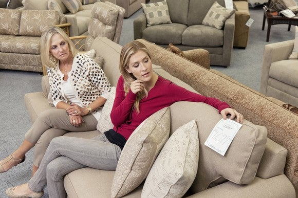 Two women sit on a couch