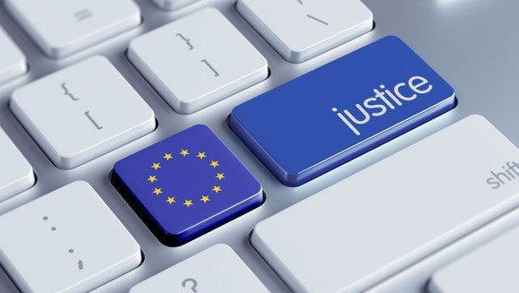 """Off-white computer keyboard where the blue """"enter"""" key contains the word """"justice"""" instead and the apostrophe key has been replaced by a European Union flag."""