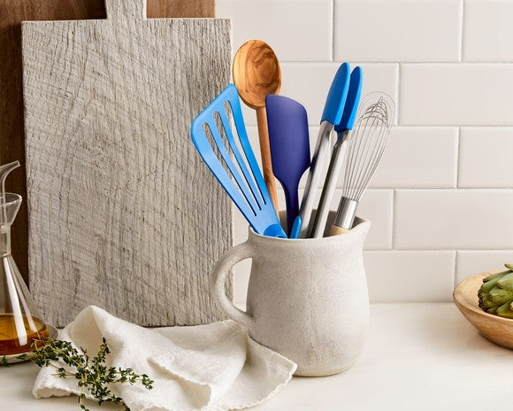 Spatulas, a whisk, and a wooden spoon, in a jar sitting on a counter.