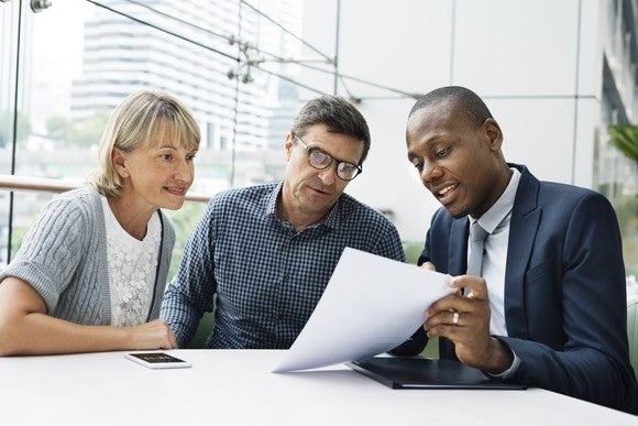 A financial advisor sitting at a table with clients.