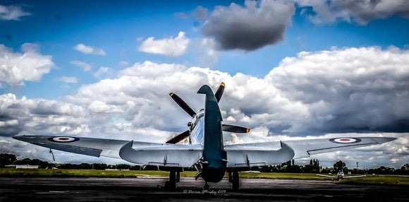 A British Spitfire, a World War II fighter plane, sits on a runway against blue sky with clouds.