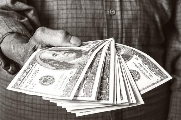 The hand of an elderly man holding a dozen $100 bills.