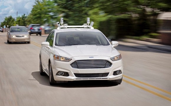 A Ford sedan driving on the road with sensors on top of the car.