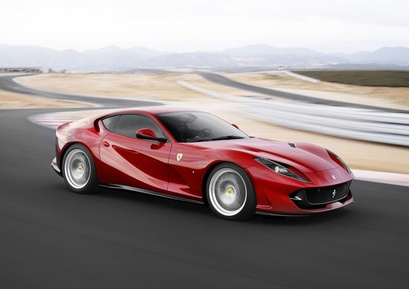 A red Ferrari 812 Superfast sports car at speed on a winding road.