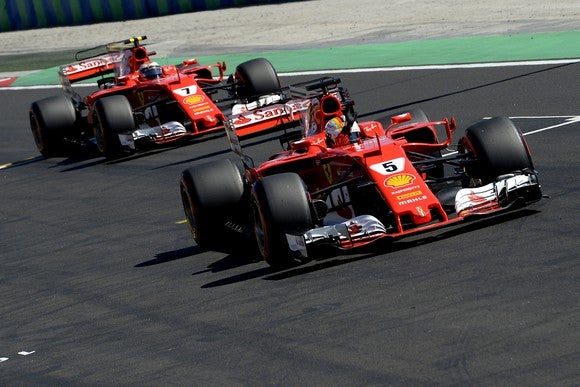 Two red Ferrari Formula 1 racing cars, numbered 5 and 7, on track at the Hungarian Grand Prix.