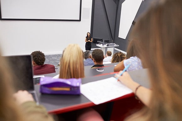 Woman lecturing in a classroom setting.