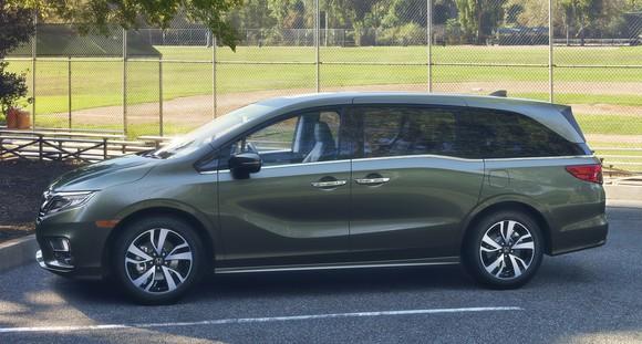 A green 2018 Honda Odyssey minivan is parked next to a baseball field.
