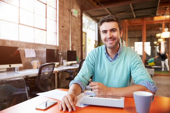 30-something man sitting at a table in an office setting