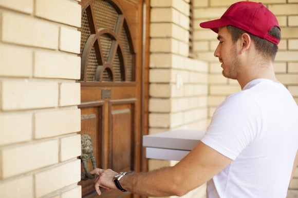 A pizza deliveryman rings a doorbell.