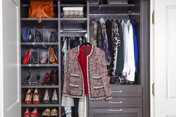 Closet with organizational system including shoes, blouses, dresses, and drawers for accessories.