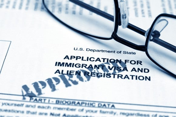 A pair of glasses sits on an approved application for immigration.