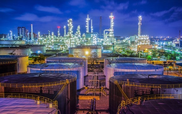 Oil storage terminals in front of refinery at night