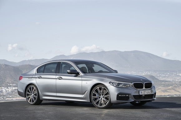 A silver BMW 5 Series sedan parked outdoors in bright sunlight, with mountains visible in the background.