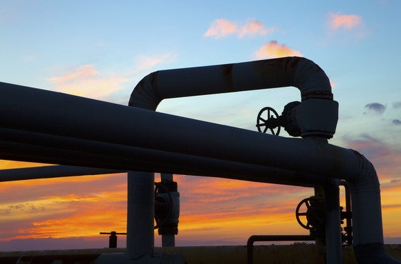 Sunset through the twists of a pipeline system.