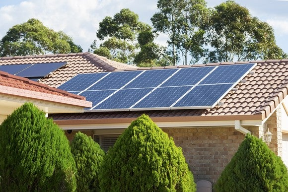 Rooftop solar system on a home with trees in the background.