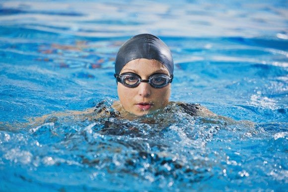 Young female swimmer wearing goggles and a head cap is treading water in a swimming pool.
