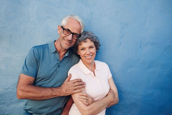 Mature man and woman hugging and smiling