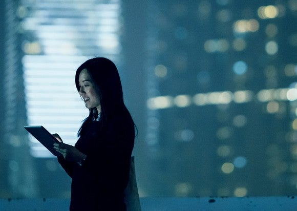 Person looking at a handheld mobile device with a city background.