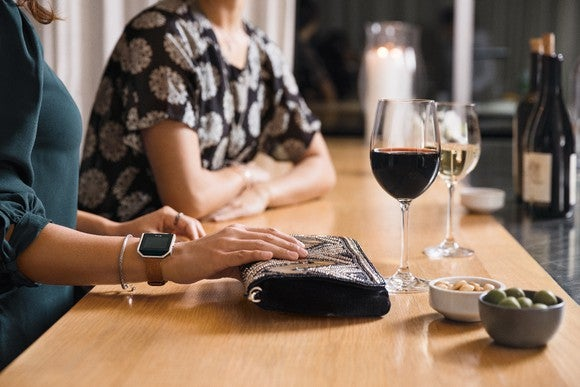 Woman wearing a Fitbit Blaze and drinking wine
