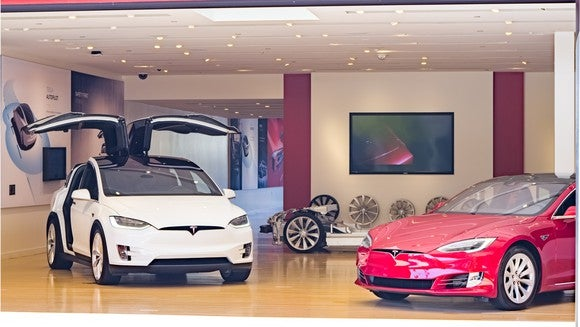 Tesla store with a white Model X and red Model S.