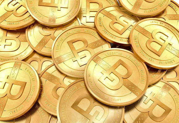 Pile of golden coins embossed with the Bitcoin logo.