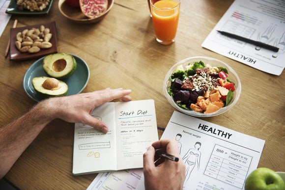 A man making notes in a notebook with dishes of healthy foods around the table.