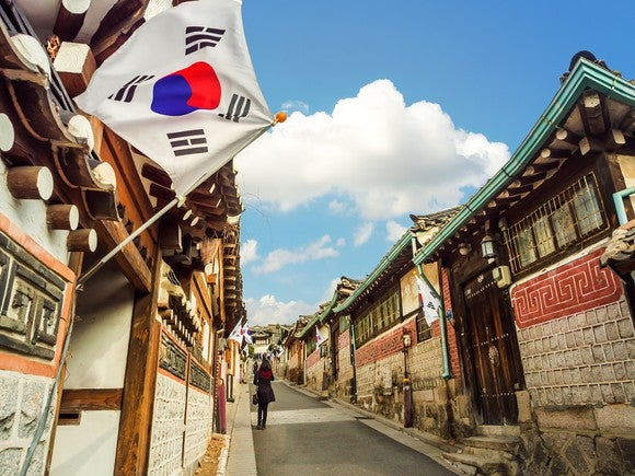 South Korean flag flying over a small street with buildings.