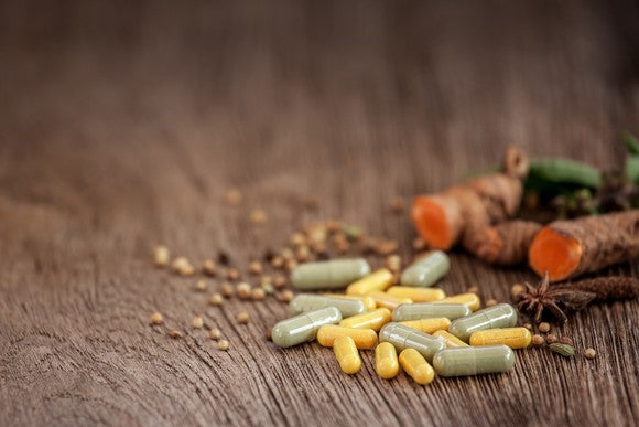 Supplement pills sitting on a wood-grain table.