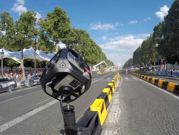 GoPro camera mounted on a barrier at a road race.