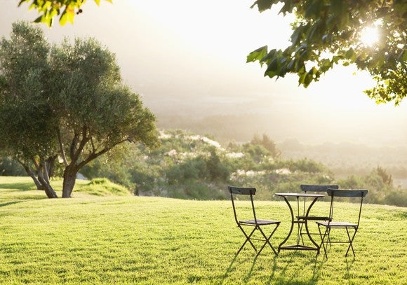 The sun shines through the leaves of a tree onto a green backyard and casts shadows on a round table and three chairs.