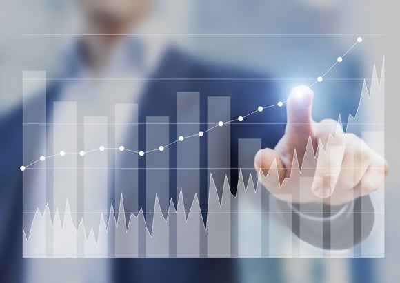 Man touching a bar chart with his index finger.
