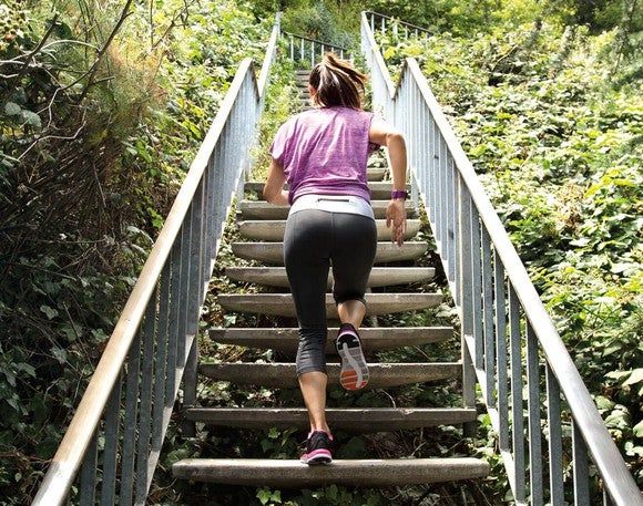 Woman in workout gear running up stairs with a Fitbit bracelet.