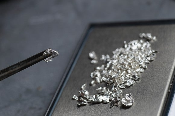 Shavings of platinum rest on a metal sheet in the background, while forceps hold a sizable piece in the forefront.