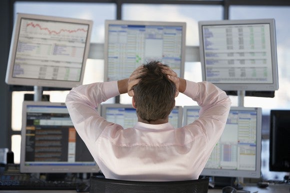 An investor grasping his head in frustration in front of multiple computer screens.