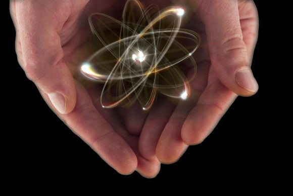 Hands cupped around an image of an atom