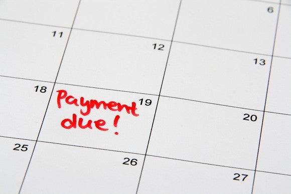 "A close up on a calendar with ""payment due!"" written on the 19th."