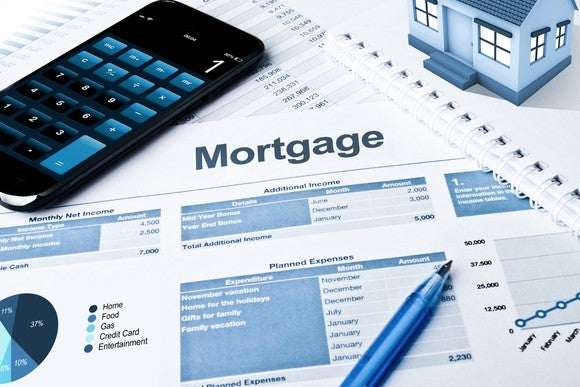 Mortgage statement with calculator, pen, and house model.