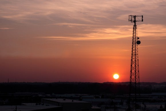 The silhouette of a cell phone tower shot against the setting sun.