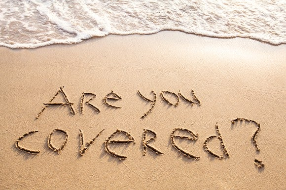 """Are you covered?"" carved into the sand on the beach."
