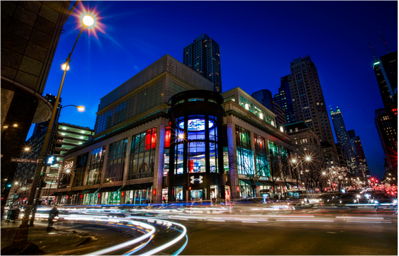 A lighted Under Amrour multi-story store in downtown Chicago on a corner at night, time laps photo shows lights blurred from cars traveling through the intersection in front of the store.