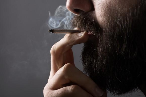 A bearded man smoking a cigarette