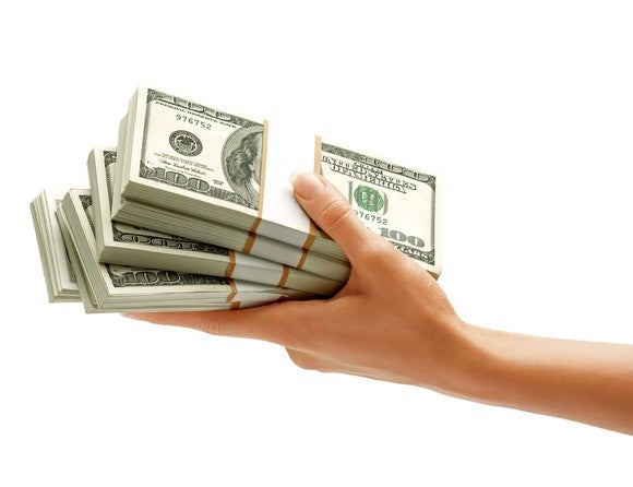a hand holding a stack of bundles of hundred dollar bills