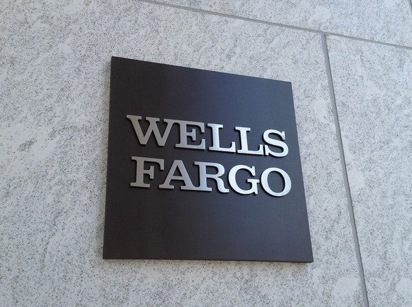A Wells Fargo sign affixed to a marble wall.