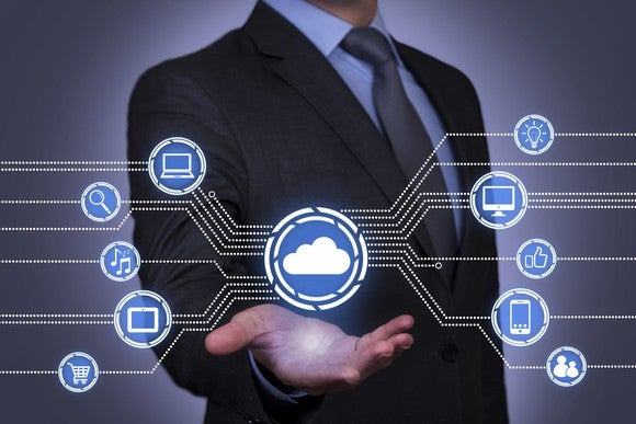Businessman holding out his hand under a cloud image that's connected to other icons depicting various technologies and consumer services.