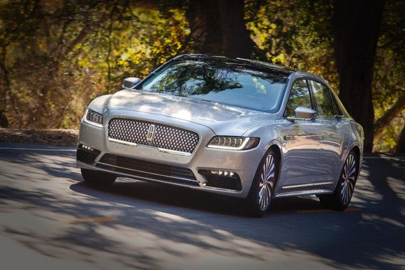 A silver Lincoln 2017 Continental driving on a road against a backdrop of autumn-leaved trees.