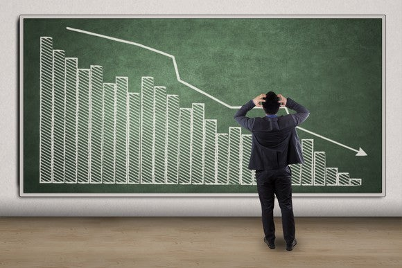 An arrow showing the downward trend of a chart on chalkboard with a business man in front of it.