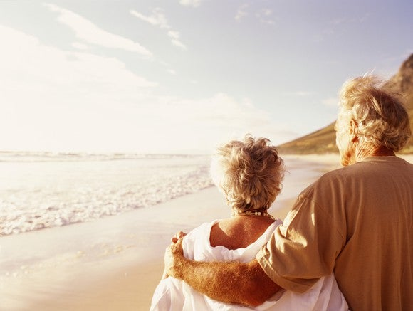 Elderly man and woman standing on beach looking at sunset with their arms around each other