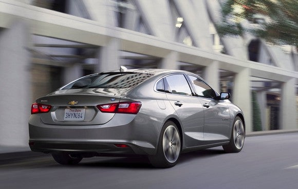 A 2017 Chevrolet Malibu Hybrid sedan in silver, driving past a white-framed commercial building.