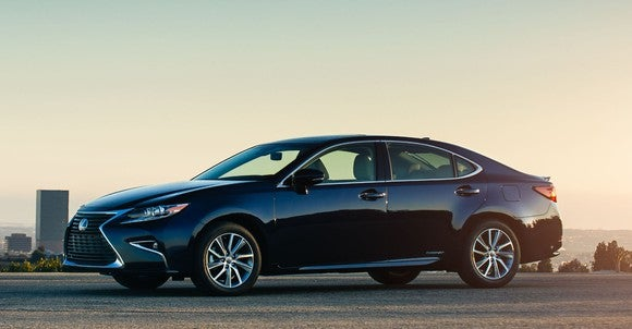 A black 2017 Lexus ES 330h sedan, in early morning light with a city in the background.