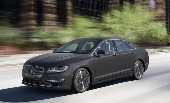 A 2017 Lincoln MKZ in dark gray on a wooded road.